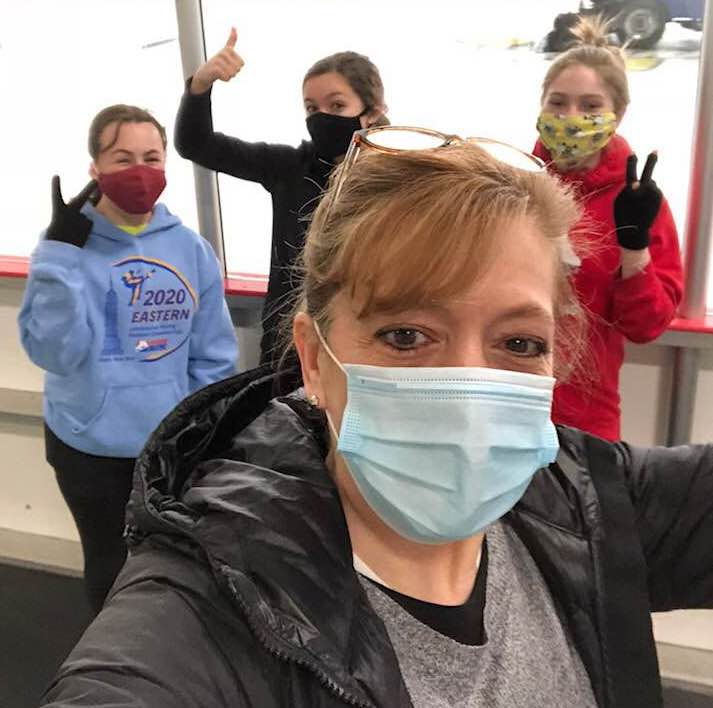 Three figure skaters and their coach, all wearing masks and giving thumbs-up.